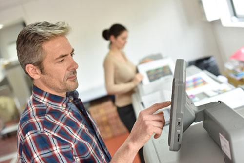 Mann und Frau an Maschine in Druckerei